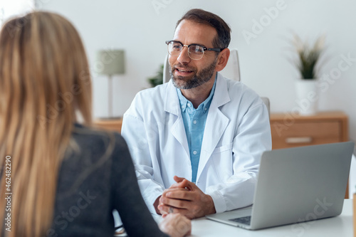 Obraz na płótnie Shot of handsome mature male doctor talking while explaining medical treatment to patient in the consultation