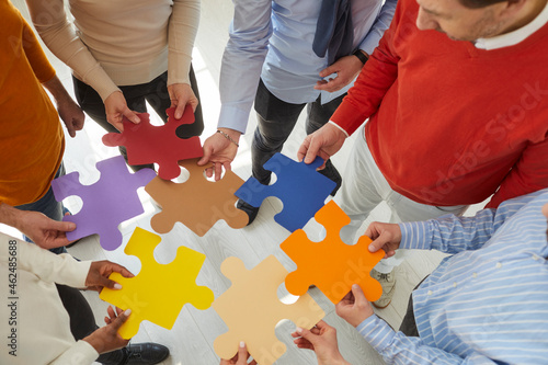 Team of creative people and business colleagues meeting in office and joining colorful jigsaw puzzle pieces. Close up. Concept of teamwork and looking for solutions together