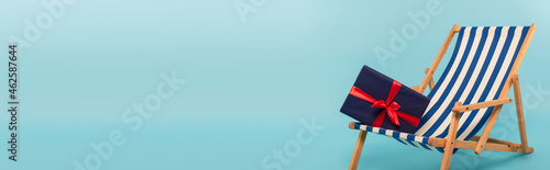 Canvas present on striped deck chair on blue background, banner