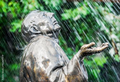Pomnik w parku na tle drzew. Padający deszcz z fontanny.