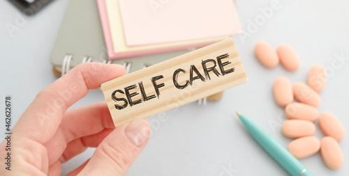 Fotografie, Obraz Self care words printed on wooden blocks, self treatment concept, blue backgroun