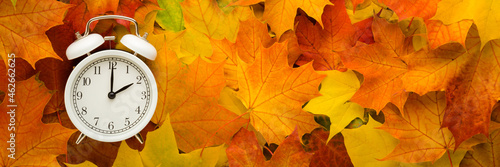 White alarm clock on colorful maple leaves background. Closeup. Time change concept. Wide banner. Empty place for text. Top down view.