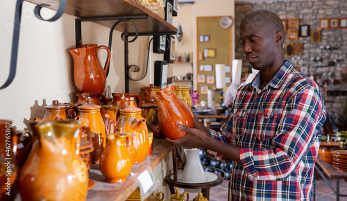 Foto Portrait of customer of pottery shop looking for stoneware in modern pottery wor