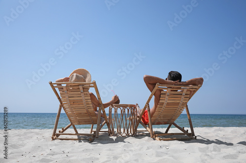 Canvas-taulu Couple resting in wooden sunbeds on tropical beach