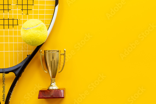 Small golden trophy cup with tennis racket and ball. Sport champion winner concept
