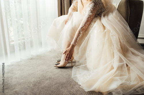 Bride with lace dress puts on her wedding shoes and straightens them with her ha Fotobehang