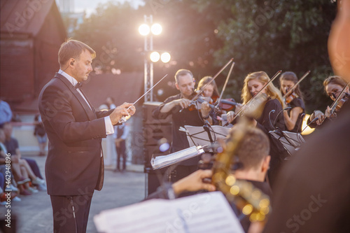 Photo Male conductor directing orchestra performance on the street