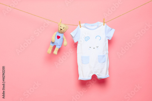 Baby clothes on a clothesline on pink background . Fototapeta