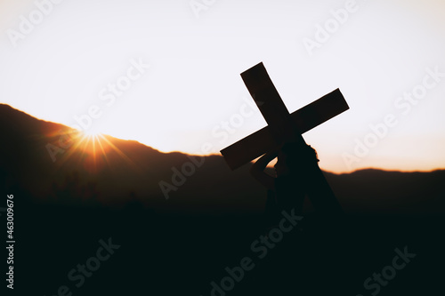 Fotografiet Girl with a carrying a cross on his back at sunset, christian silhouette concept