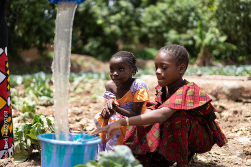 Fotografiet Two little black African girls in brightly colored clothes sitting on an arid ca