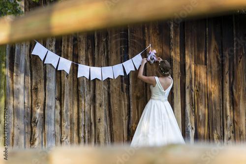 Billede på lærred Bride in a beautiful bridal dress hanging wedding decorations on the wall