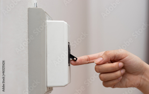 Tela Close-up of a woman's hand pushing a breaker switch to turn on a house light on a white wall