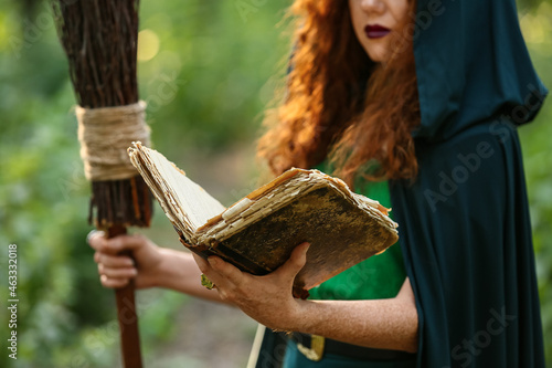 Fotografie, Obraz Young witch with spell book in green forest