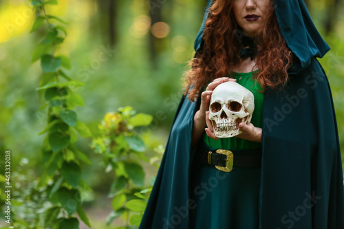 Obraz na plátně Young witch with skull in green forest