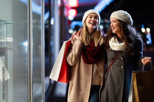 Portrait of happy women friends enjoying shopping together outdoors. Christmas shopping