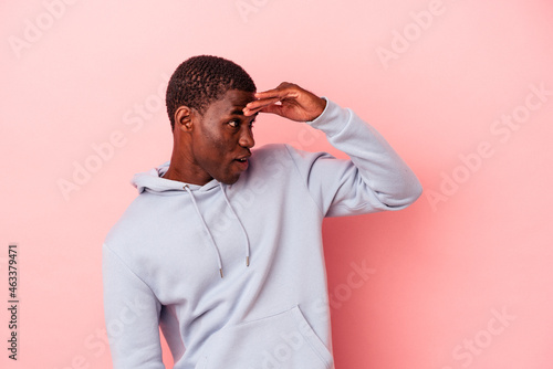 Young African American man isolated on pink background looking far away keeping hand on forehead.