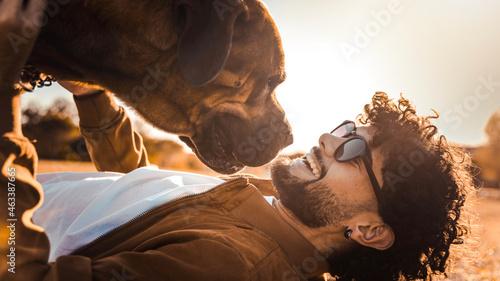 Obraz na plátně Happy man having fun playing with dog at park - Guy cuddling labrador retriever