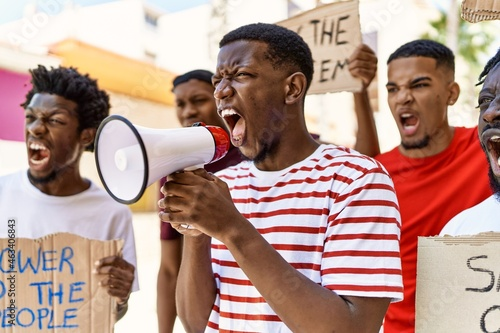 Valokuvatapetti Group of young african american activists protesting holding banner and using megaphone at the city