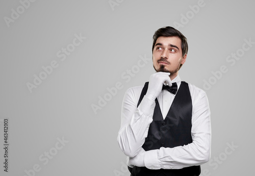 Canvas Print Waiter in uniform touching chin on gray background