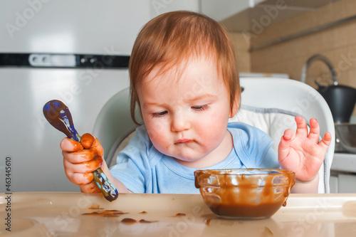 Handsome red-haired baby eating in children's chair Fototapeta