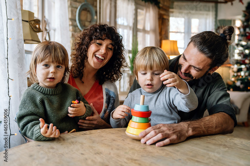 Family and childhood concept. Young parents spending time together with children at home.