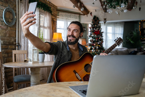 Portrait of a man taking guitar lessons online in a room at home