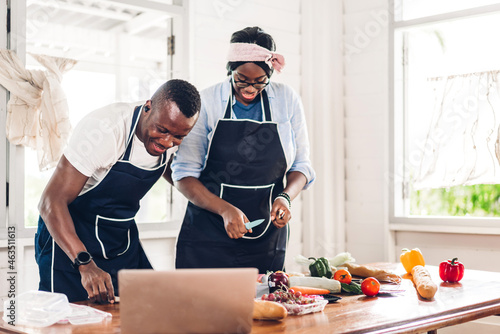 Murais de parede Portrait of love african american couple having fun cooking together and looking
