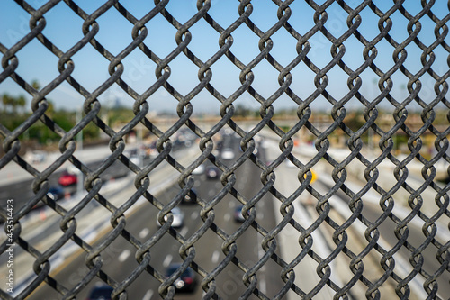 California freeway viewed from behind overpass fence #463514423