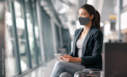 Travel during coronavirus. Asian business woman wearing face mask in airport terminal waiting for flight thinking looking out the window using phone app for vaccine passport.