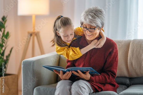 Grandmother reading a book to granddaughter.
