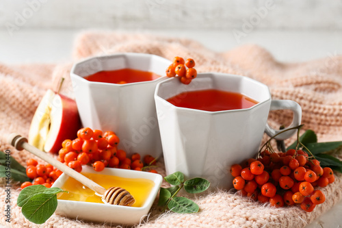 Composition with cups of tasty rowan tea, berries and honey on table, closeup
