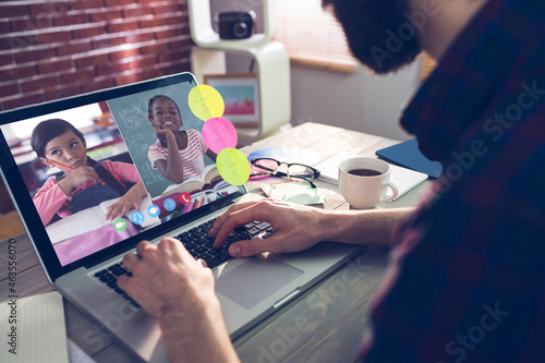 Caucasian man using laptop for video call, with smiling diverse elementary school pupils on screen