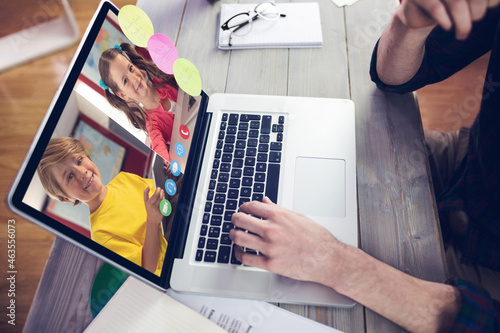Hands of man using laptop for video call, with smiling caucasian elementary school pupils on screen