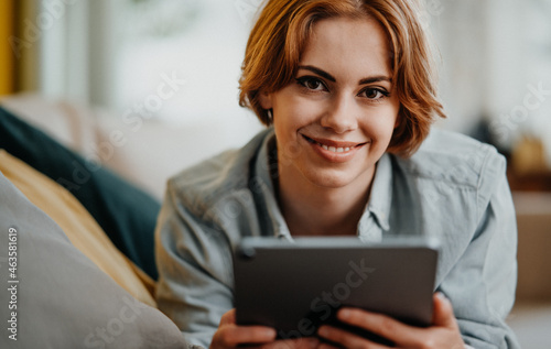Portrait of happy young woman using tablet, lying on sofa at home, looking at camera