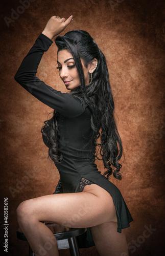 Obraz na plátně Attractive long hair model with black tight dress  posing provocatively