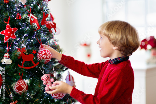 Kids decorate Christmas tree. Child on Xmas eve.