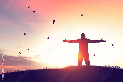 Fotografiet Man rising hands and birds flying on sunset sky at nature field abstract background