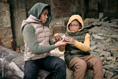 Two hungry girls from refugee camp sharing peach while sitting on ruins of build Fototapeta