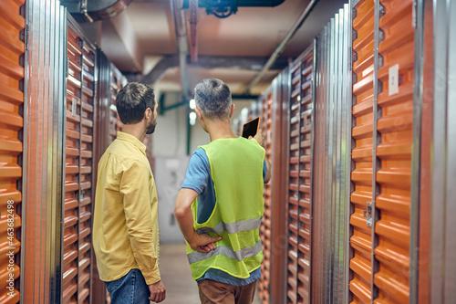 Obraz na plátně Two men talking in warehouse between garages