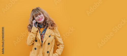woman on the street with mobile phone and yellow wall