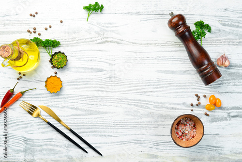 Cutlery, spices and vegetables on a white wooden background. Restaurant menu. Top view.