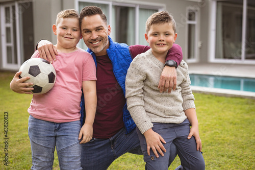 Portrait of caucasian father and two sons smiling while holding football in the garden