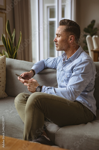 Thoughtful caucasian man using smartphone sitting on the couch at home