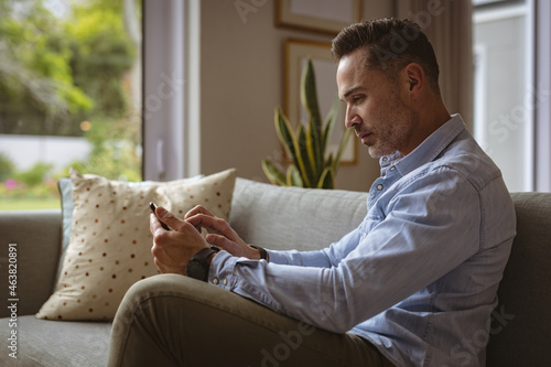 Caucasian man using smartphone sitting on the couch at home