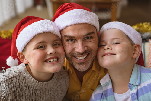 Portrait of caucasian father and two sons wearing santa hat smiling at home during christmas