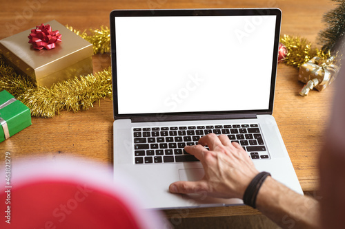 Mid section of man wearing a santa hat using laptop with copy space at home during christmas