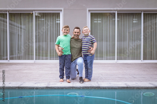 Portrait of caucasian father and two sons holding hands smiling while standing near the pool