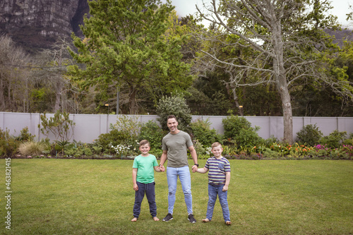 Portrait of caucasian father and two sons holding hands smiling while standing in the garden