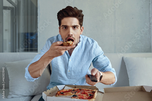 Man resting, eating pizza and watching television