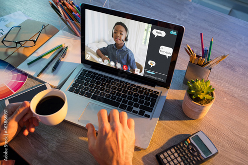 Hands of man using laptop for video call, with african american elementary school pupil on screen